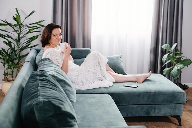 Mujer bebiendo café o té en casa acogedora por la mañana