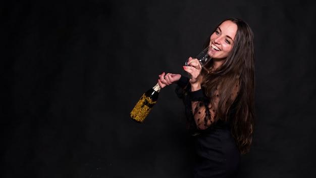 Mujer bebiendo champán de vidrio