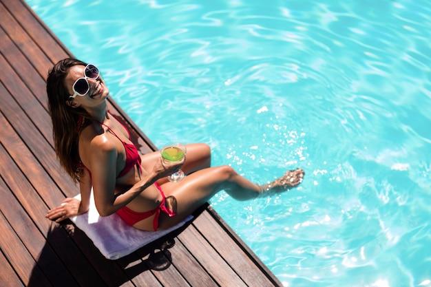 Mujer bebiendo cócteles en el borde de la piscina