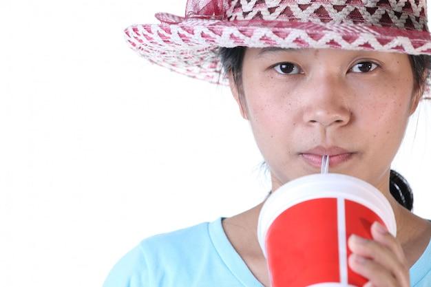 Mujer bebiendo cola a través de una pajita con vidrio rojo