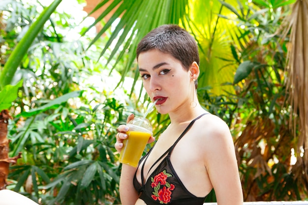 Mujer bebiendo un jugo verde en una selva tropical