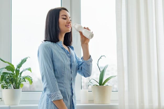 Mujer bebiendo leche bebe yogur de una botella