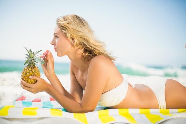 Mujer bebiendo de una piña