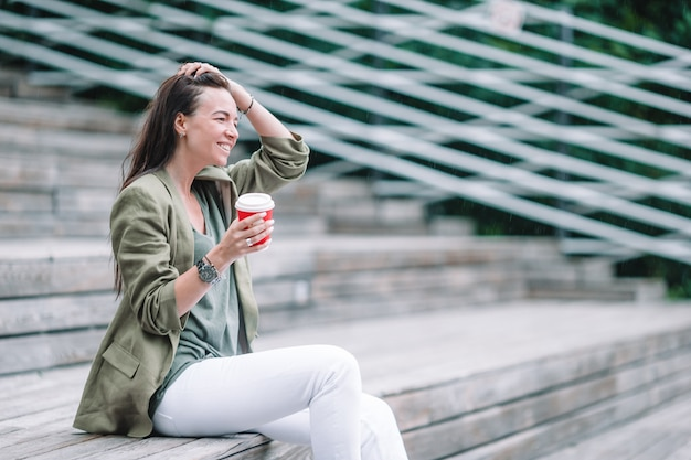 Mujer bebiendo sabroso café al aire libre en el parque