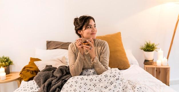 Mujer bebiendo su té en la cama