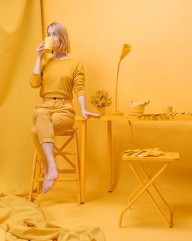 Mujer bebiendo de una taza en un escenario amarillo