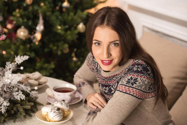 Mujer bebiendo té cerca de árbol de navidad