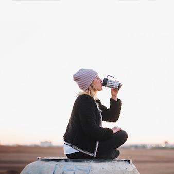 Mujer bebiendo del termo en la naturaleza
