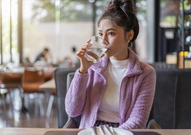 Mujer bebiendo un vaso de agua en el restaurante