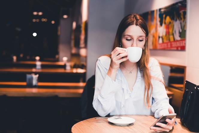 Mujer bebiendo y usando el teléfono inteligente