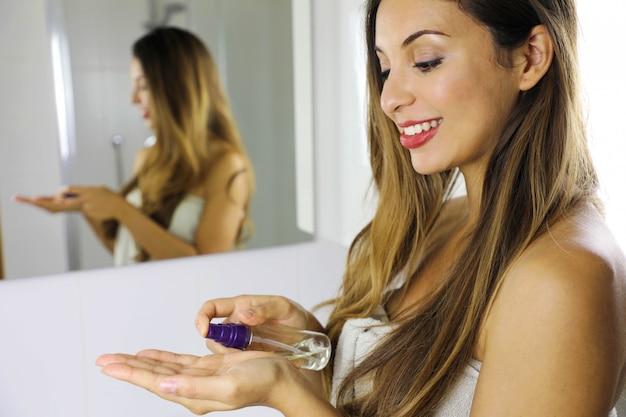 Mujer de belleza con aceite limpiador ecológico para quitar el maquillaje