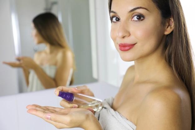 Mujer de belleza con aceite limpiador para quitar el maquillaje