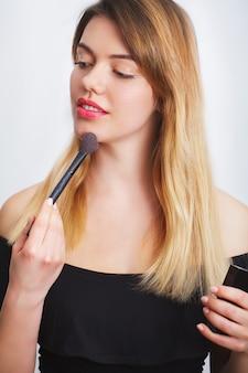 Mujer de belleza aplicando maquillaje
