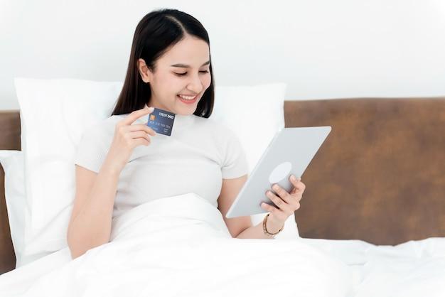 Mujer de belleza asiática utiliza una tarjeta de crédito para realizar compras usando una tableta a través de internet con una cara sonriente feliz, siendo un nuevo negocio en línea normal en la experiencia de compra desde casa.