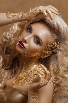 Mujer de belleza, cabello rubio, maquillaje profesional, color dorado.