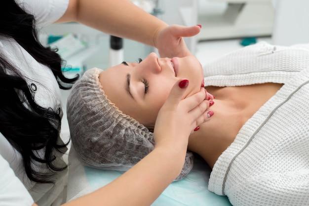Mujer de belleza con masaje cosmético, tratamiento facial, de cerca.