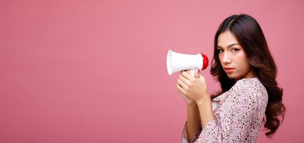 La mujer de la belleza de la moda tiene el pelo largo y negro que expresa la emoción que siente sexy. retrato de niña asiática usa vestido rosa y sostenga el megáfono para anunciar sobre la pared rosa, espacio de copia