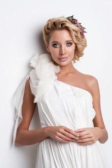 Mujer de la belleza con el peinado y el maquillaje de la boda.