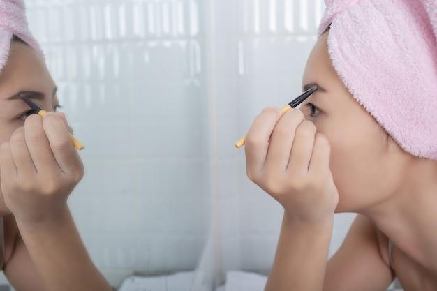Mujer de la belleza que aplica maquillaje.