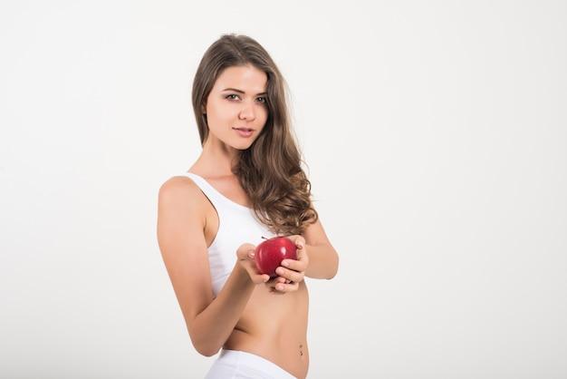 Mujer de la belleza que sostiene la manzana roja mientras que está aislada en blanco