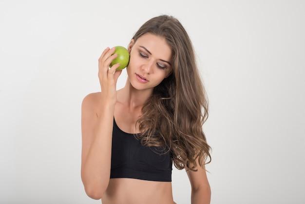 Mujer de la belleza que sostiene la manzana verde mientras que está aislada en blanco