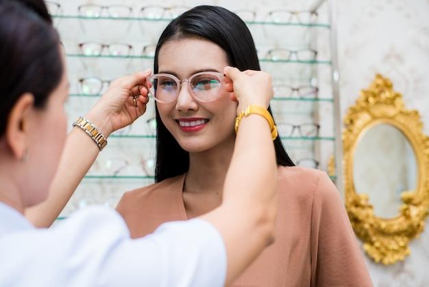 Mujer de belleza sonríe y usa lentes con optometrista.