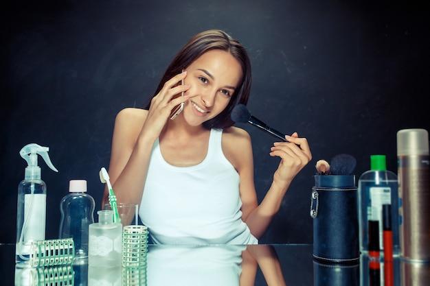 Mujer de belleza con teléfono móvil aplicando maquillaje. hermosa chica mirando en el espejo y aplicando cosmético con un pincel grande. modelo caucásico en el estudio