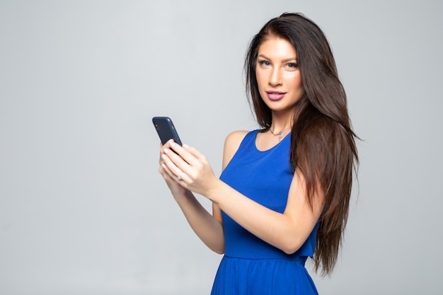 Mujer de belleza usando y leyendo un teléfono aislado