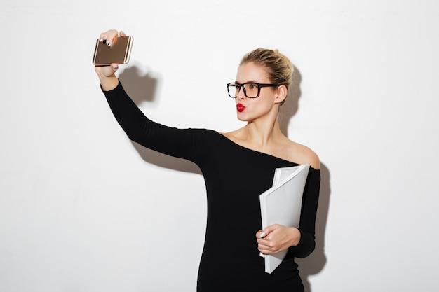 Mujer de belleza en vestido y anteojos haciendo selfie en smartphone