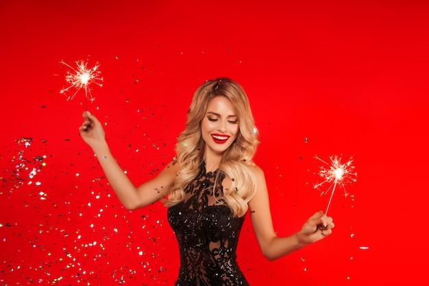 Mujer con bengala celebrando la fiesta de año nuevo. retrato de hermosa niña sonriente en vestido negro brillante lanzando confeti
