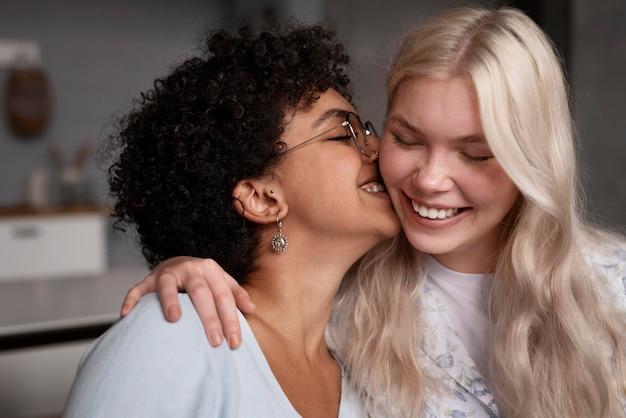 Mujer besando a su novia en la mejilla