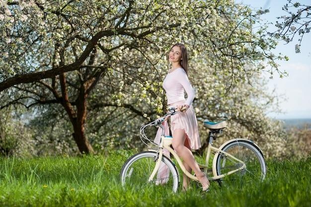 Mujer en bicicleta en el jardín de primavera.