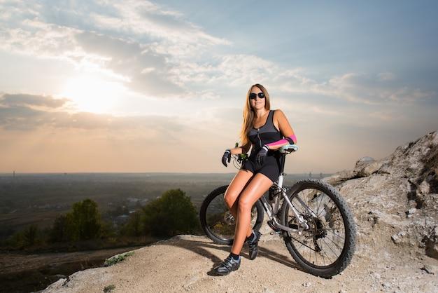 Mujer con la bicicleta de montaña en el acantilado de roca bajo un cielo al atardecer