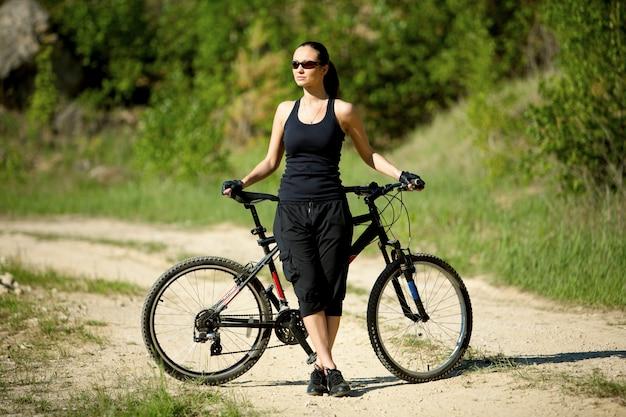 Una mujer con una bicicleta de montaña disfruta de la vista