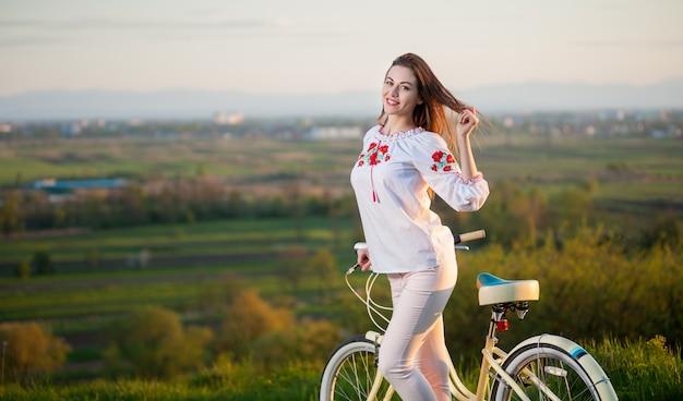 Mujer con bicicleta retro en la colina en la noche