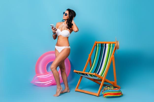 Mujer bien formada con smartphone de pie junto a la tumbona