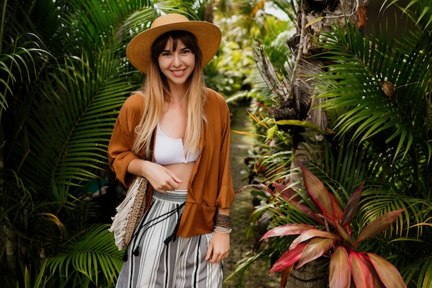 Mujer bien vestida en perfecto estado de ánimo posando juguetonamente en un jardín tropical.