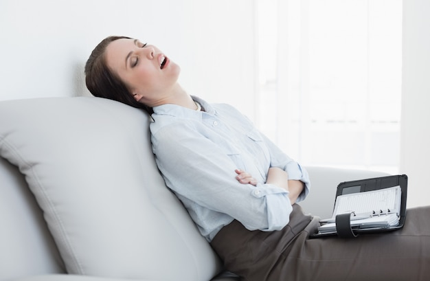 Mujer bien vestida, sentada y durmiendo en el sofá