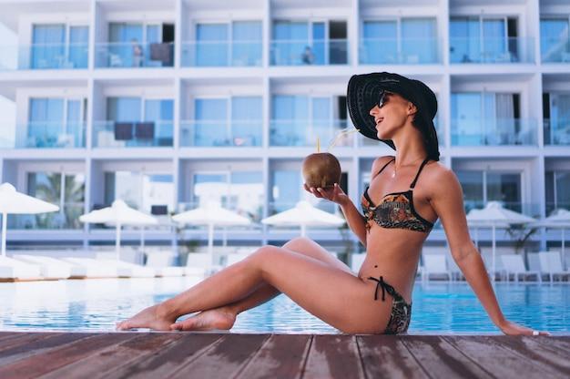 Mujer en bikini bebiendo leche de coco en la piscina