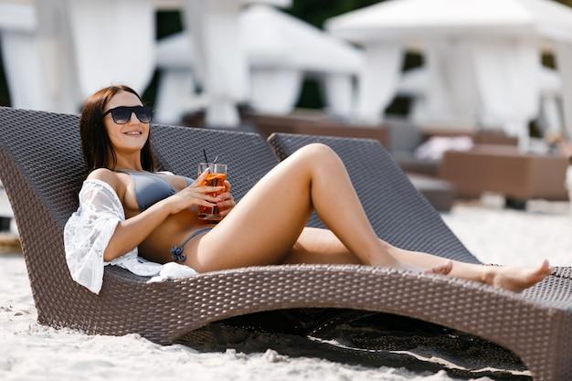 Una mujer en bikini bronceada y tumbada en una tumbona