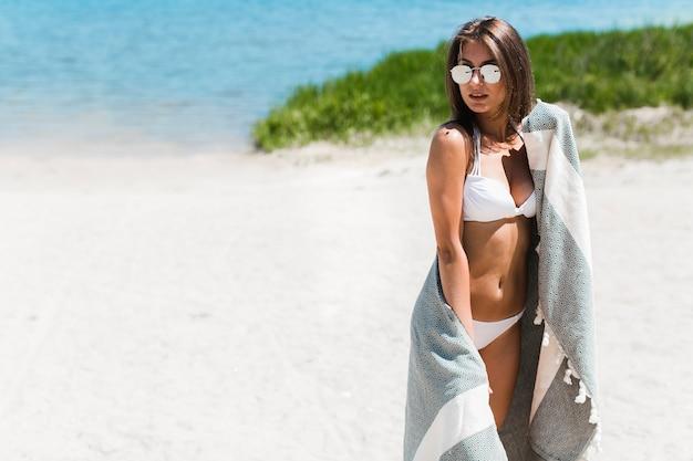 Mujer en bikini y bufanda de playa
