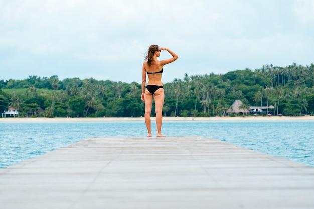 Mujer en bikini caminando por un embarcadero tropical