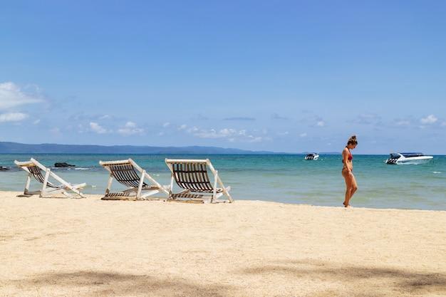 Mujer con bikini y caminando por la playa del lado derecho.