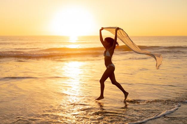 Mujer en bikini corriendo con bufanda en la playa