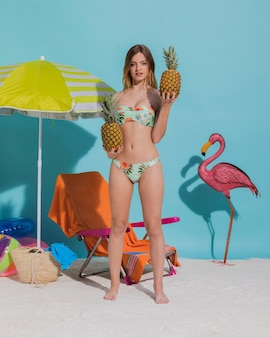 Mujer en bikini con frutas exóticas.