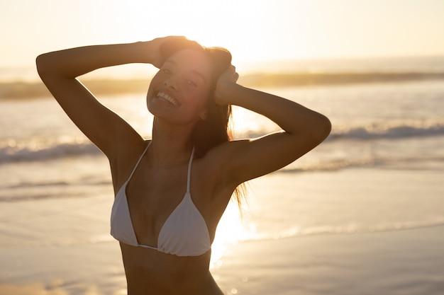 Mujer en bikini con las manos en la cabeza de pie en la playa.