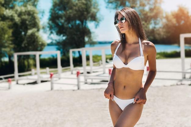 Mujer en bikini manteniendo las manos en las caderas