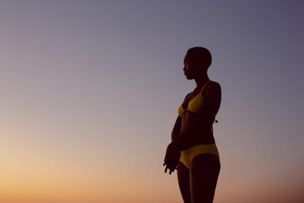 Mujer en bikini de pie en la playa