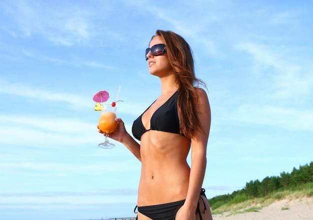 Mujer en bikini en la playa con cóctel fresco de verano