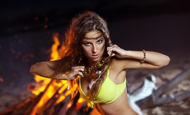Mujer en bikini posando junto a una hoguera